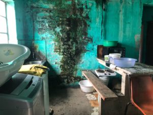A very rough looking kitchen area, very dirty and poor looking