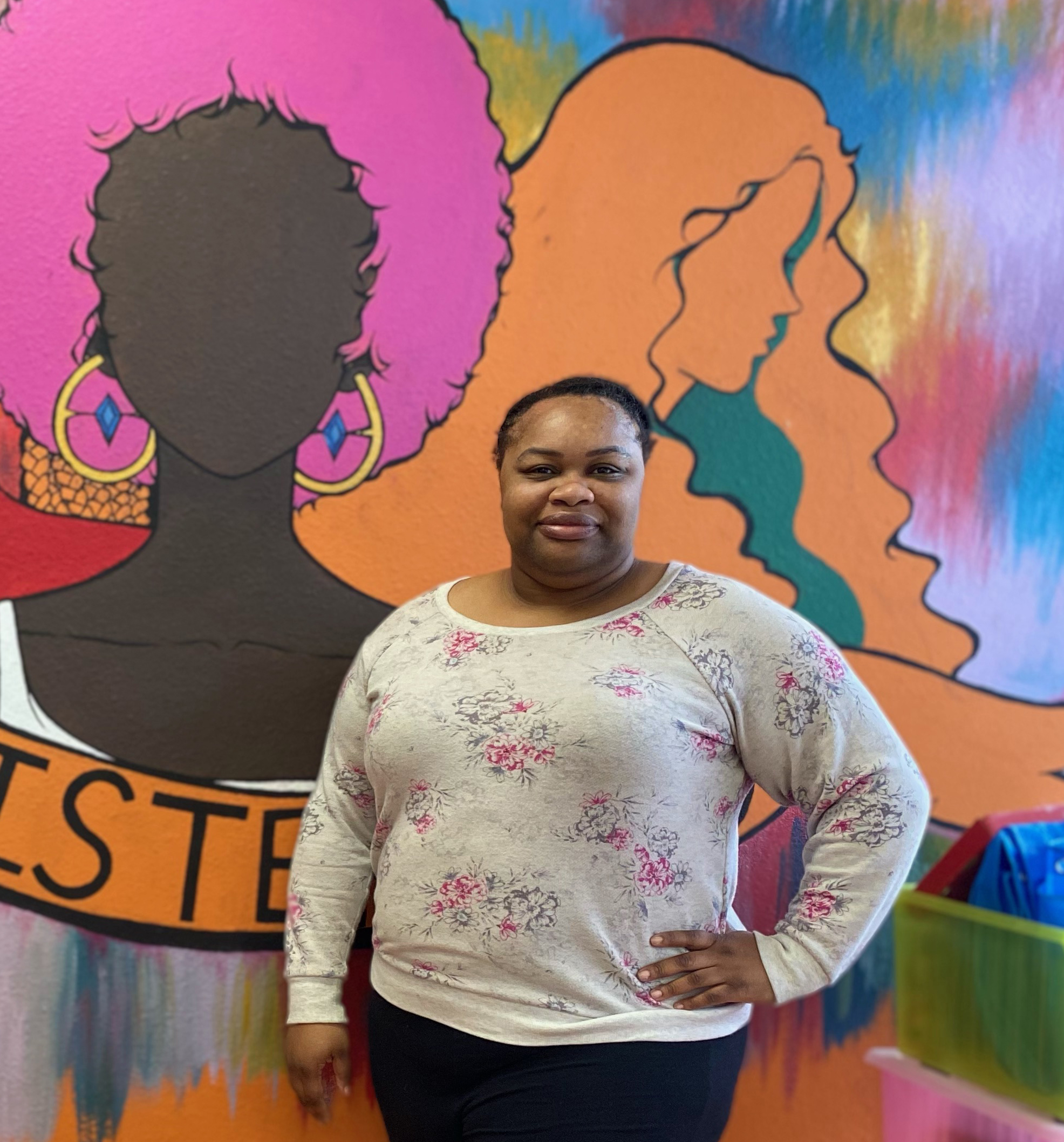 Jamila Coleman in front of colorful painting
